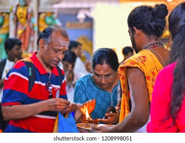 Little India, Singapore 25.08.2017. People praying at Hindu temple Sri Veeramakaliamman with Brahman priest, burning incense.