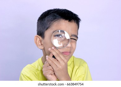 little indian boy holding magnifying glass