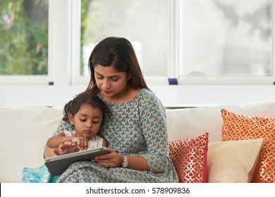 Little Indian girl sitting on sofa with her pretty mother and playing game on digital tablet against panoramic windows