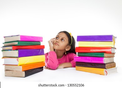 little indian girl thinking or dreaming during preparing homework