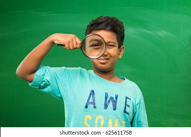 little indian/asian boy holding magnifying glass standing isolated over green chalkboard background