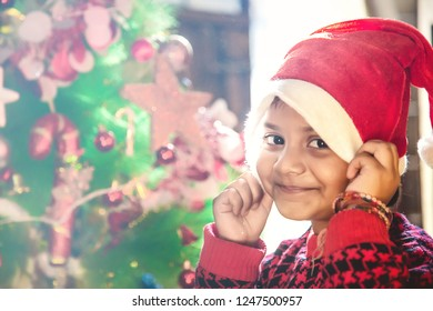 Little Indian/Asian kid girl in santa hat with Christmas tree and lights on background.