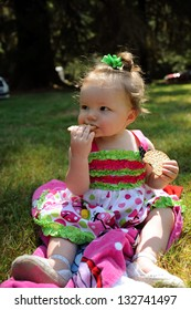 Little infant girl eating a cracker while dressed up and enjoying a summer picnic.