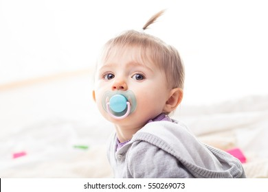 little infant girl with her blue pacifier and a funny tuft posing as a fashion model