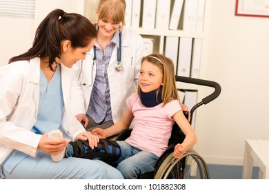 Little injured girl on wheelchair with doctors at medical office