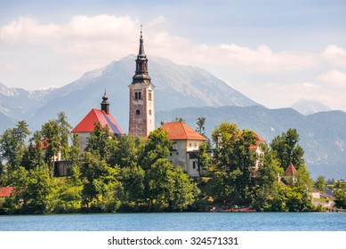 Little Island with Catholic Church on Bled Lake, Slovenia with Mountains in Background