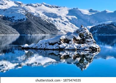 Little island in mountain lake with snow covered lake shores. Garibaldi Lake. Whistler. British Columbia. Canada
