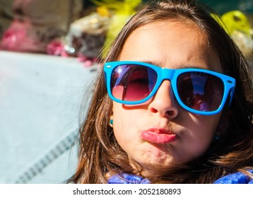 Little Italian girl with sun glasses and funny face expression. Happy family moments.