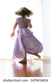Little Japanese girl dancing with her princess dress on a wooden floor.