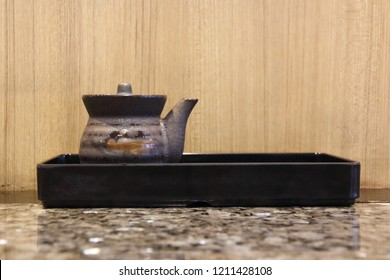 A little Japanese pottery in a dark tray on the marble table with wooden wallpaper in the background. Cute Soy sauce storage. Restaurant. Acrylic pot/kettle. Kintsugi.