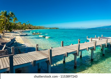 Little jetty and boat on tropical beach with amazing water, Moorea, Tahiti