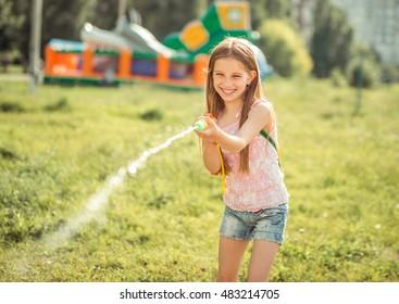 little joyful girl playing with water gun outside