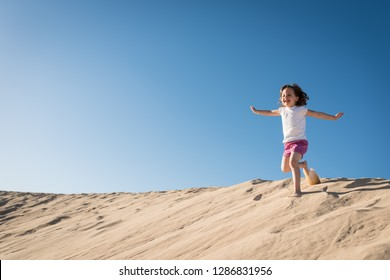 Little joyful girl running down sand dune on sunny day with clear blue sky