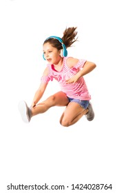 Little jumping caucasian girl with a headphones on white background