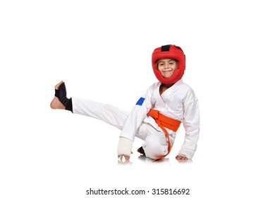 little karate girl sitting on the floor with a raised leg