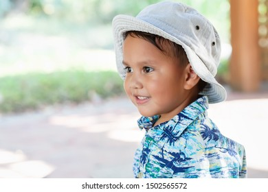 A little kid; 3 year old, wearing a hat and hawaiian print shirt, looking off into the distance with a cute smile on face.