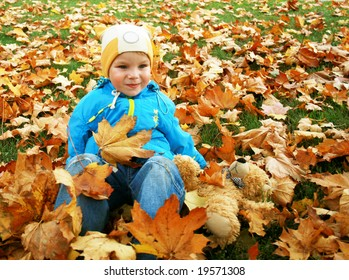 Little kid in autumn leaves