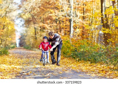 Little kid boy of 3 years and his father in autumn forest with a bicycle. Dad teaching his son. Active family leisure. Child with helmet. Safety, sports, leisure with kids concept.