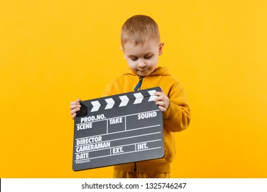 Little kid boy 3-4 years old in yellow clothes isolated on orange wall background, children studio portrait. People childhood lifestyle concept. Hand hold film making clapperboard. Mock up copy space