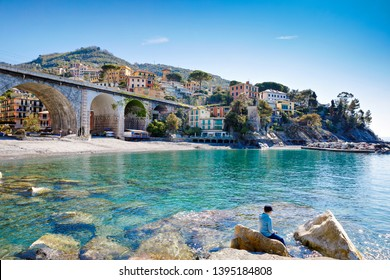 Little kid boy climbing on stones on beach of Mediterranean sea in Liguria region, Italy. Awesome landscape of Zoagli, Cinque Terre and Portofino. Beautiful Italian city with colorful houses.