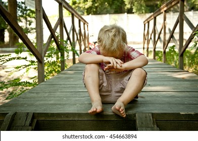 Little kid Boy crying sitting on steps in park. Loneliness, melancholy, stress, bullying, depression or frustration. Upset crying tears problem child toddler with blond hairstyle  with head in hands