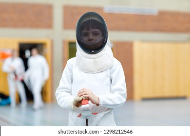 Little kid boy fencing on a fence competition. Child in white fencer uniform with mask and sabre. Active kid training with teacher and children. Healthy sports and leisure.