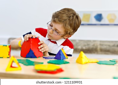Little kid boy with glasses playing with lolorful plastic elements kit in school or preschool nursery. Happy child building and creating geometric figures, learning mathematics and geometry.