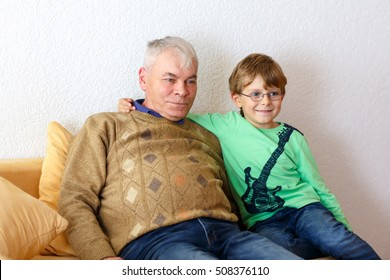 Little kid boy and grandfather watching tv at home. Preschool child and senior man enjoying cartoons on television. Sitting together on couch. people, children, television, friends and friendship
