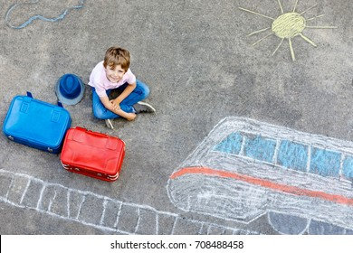 Little kid boy having fun with fast train picture drawing with colorful chalks on asphalt. Child painting with chalk and crayon and going on vacations. Schoolkid sitting on suitcase