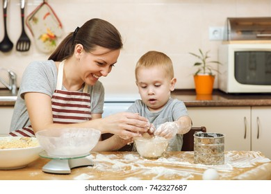 Little kid boy helps mother to cook Christmas ginger biscuit in light kitchen with tablet on the table. Happy family mom 30-35 years and child 2-3 in weekend morning at home. Relationship concept.