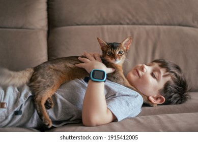 Little kid boy with his cat pet on the couch. Children and love pets concept. Friendship with aimals