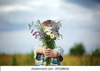 Little kid boy holding bouquet of fields flowers. Child giving flowers