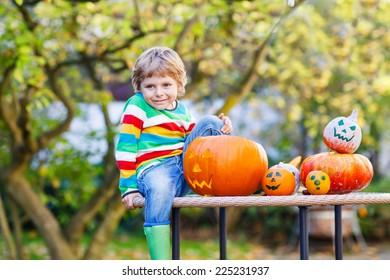 Little kid boy making jack-o-lantern for halloween in autumn garden, outdoors. Having fun on sunny warm october day