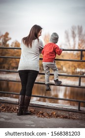 Little kid boy with mom in fashionable clothes plays in nature.