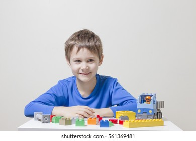 Little kid boy playing with colorful plastic construction bricks at home