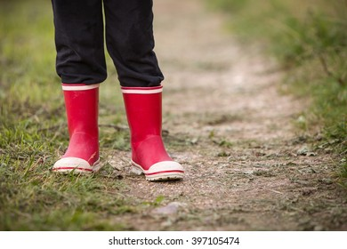 583332bd1aa little kid boy in rain rubber boots. leg s shot. Child in bright red shoes