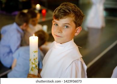 Petit garçon recevant sa première communion sainte. Joyeux enfant tenant une bougie de baptême. Tradition en église catholique. Enfant dans une robe traditionnelle blanche dans une église près de l'autel.