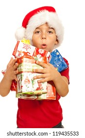 Little kid boy with santa hat holding many Christmas gifts in his arms isolated on white background