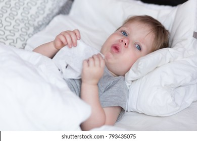 Little kid boy with sore throat cough in the bed close-up