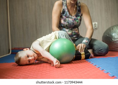 Little kid with cerebral palsy has musculoskeletal therapy by doing exercises on fit ball