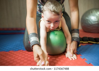 Little kid with cerebral palsy has musculoskeletal therapy by doing exercises on fit ball. Child look at camera