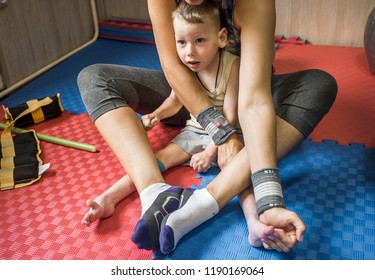 little kid with cerebral palsy has musculoskeletal therapy by doing exercises in body fixing. Load on legs