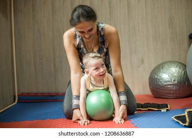 Little kid with cerebral palsy has musculoskeletal therapy by doing exercises on fit ball. Therapist help child