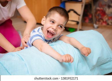 little kid with cerebral palsy has musculoskeletal therapy by doing exercises in body fixing. Load on hands,cheerful boy with disability at rehabilitation center for kids with special needs