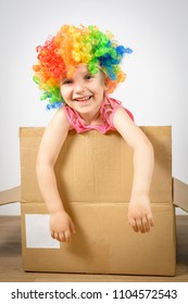 a little kid clown looks out of the box. 1 April - the concept of a fool's day