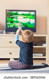 Little kid controlling the TV with the remote control