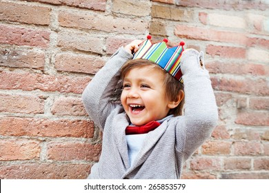 little kid with a crown on a brick wall