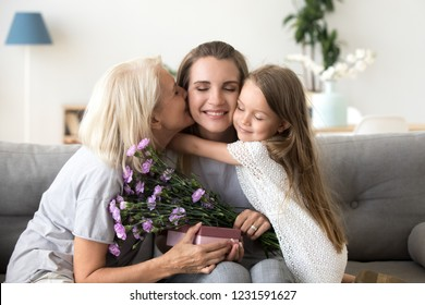 Little kid daughter and old mother kissing embracing young woman congratulating with birthday, senior grandmother and child girl presenting happy mom flowers gift box, 3 generation celebrate together