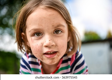 Little kid with dirty face from playing outside in the dirt and mud. Games in the nature, healthy children