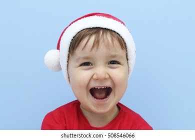 little kid dressed as Santa Claus laughing